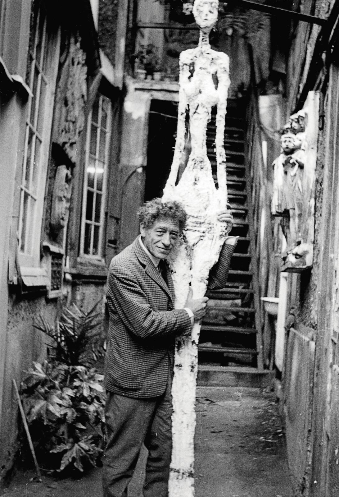 Giacometti avec Grande femmeIV dans la cour de l'atelier, août1960.