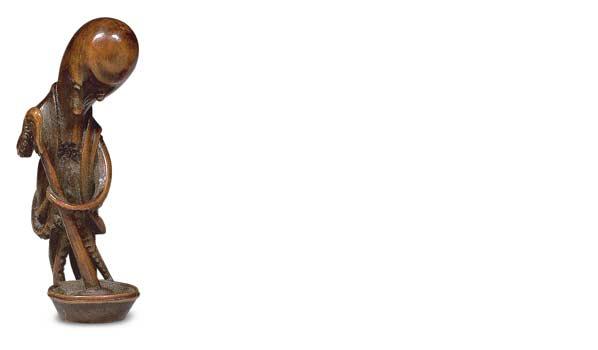 Netsuke en bois en forme de pieuvre préparant un mochi, les yeux incrustés de corne brune, signé Miwa. H. 7,2 cm.6 840 € frais compris.Paris, 27/5/200