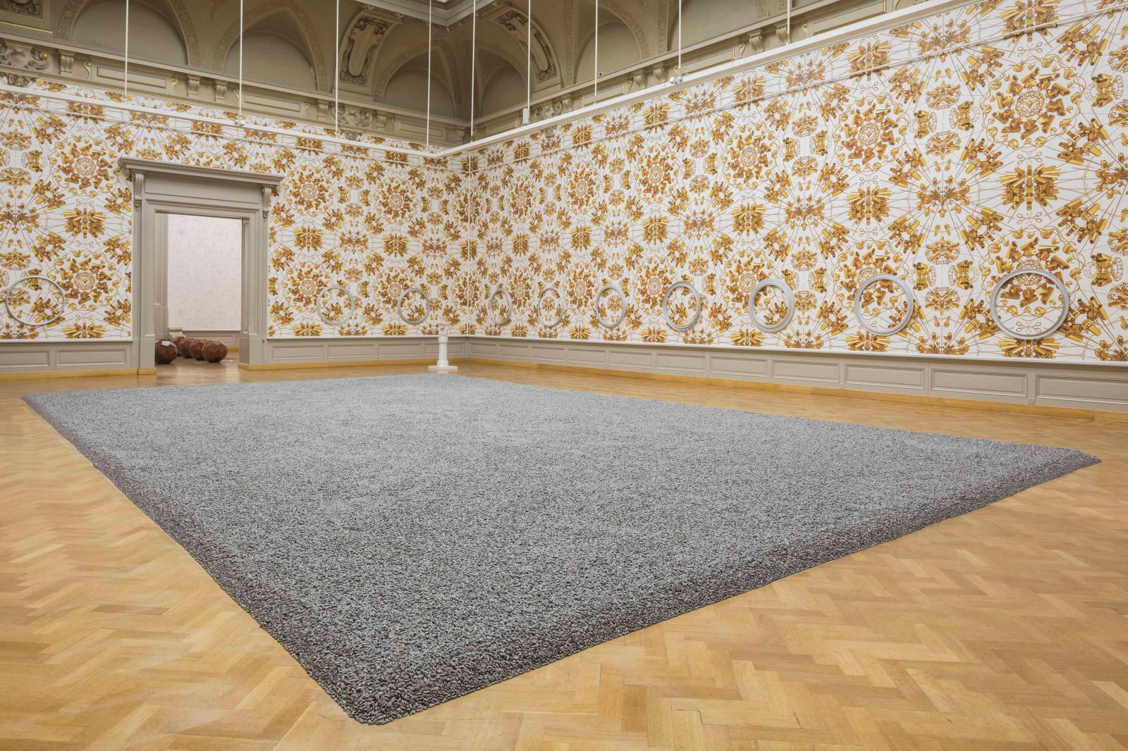 "Ai Weiwei (b. 1957), ""Sunflower Seeds"" (2010, porcelain) and ""The Animal That Looks Like a Llama but Is Really an Alpaca ""(2015, wallpaper), at the ex"