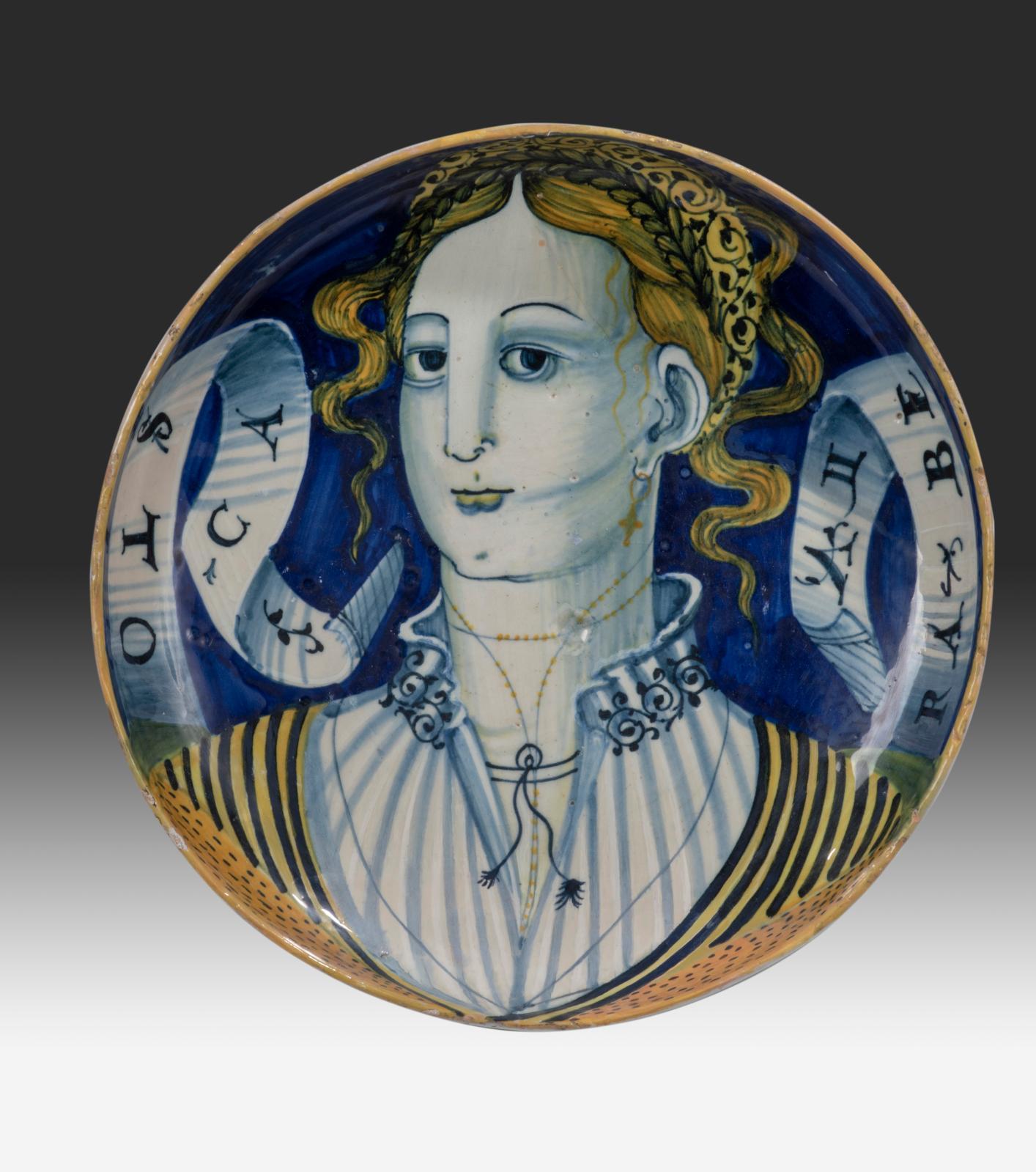 Casteldurante, XVIesiècle. Grande coupe à décor polychrome en plein sur fond bleu d'une Bella de face, inscription «TOCA RA BELLA», filet jaune sur l