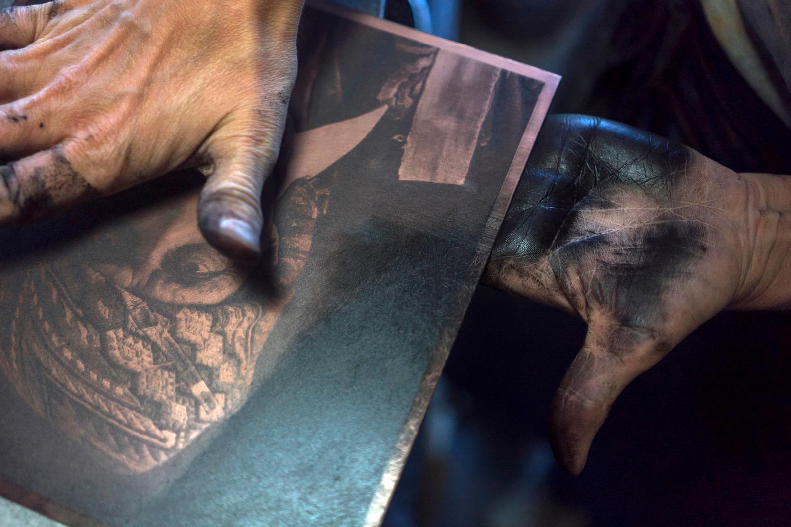 Après avoir encré la matrice et estompé le surplus avec de la tarlatane, l'artisan d'art passe ici sa main pour laisser la quantité d'encre suffisante