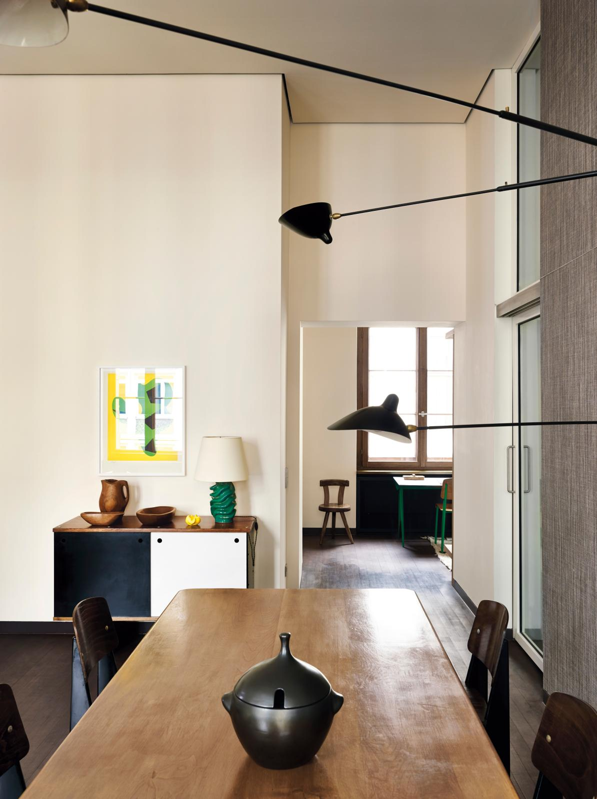 In Berlin, a table by Pierre Chapo, chairs by Jean Prouvé, sideboard by Charlotte Perriand, ceramics by Georges Jouve, wood sculpture by Alexandre Nol