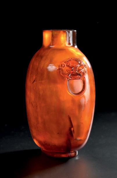 3500€ Chine, XVIIIesiècle. Flacon tabatière en ambre, deux anses en forme de tête de chimère tenant des anneaux, bouchon en verre vert, h.8,8cm.