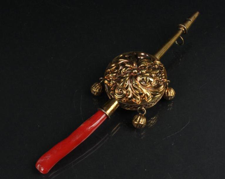 1512€ Paris, 1819-1838, hochet sifflet en vermeil de forme ronde à décor de fleur et de feuillage, la tranche ajourée retenant quatre grelots, manch