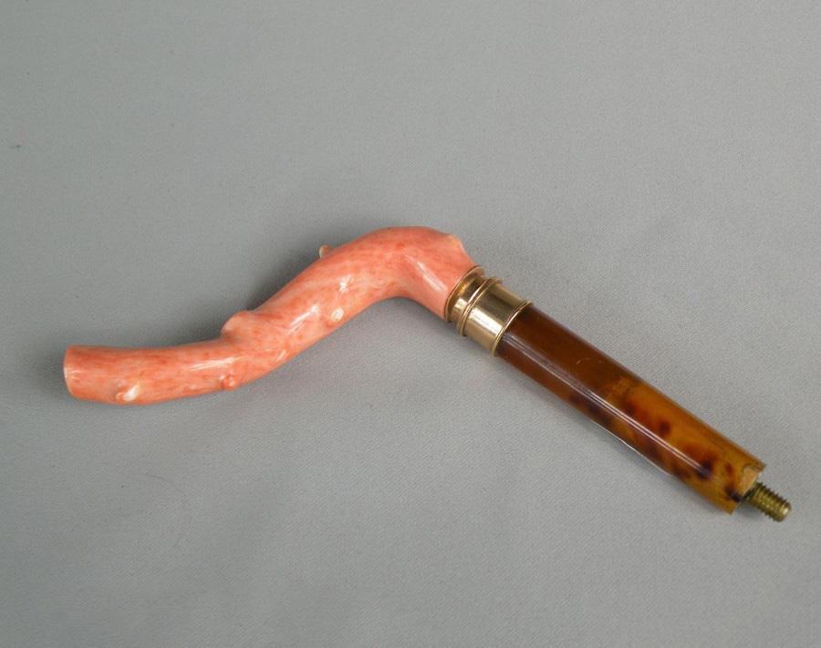 375€ Vers 1900, manche d'ombrelle en corail, bague en métal doré, h.14cm. Drouot, 10novembre2015. DaguerreOVV. M.Derouineau.