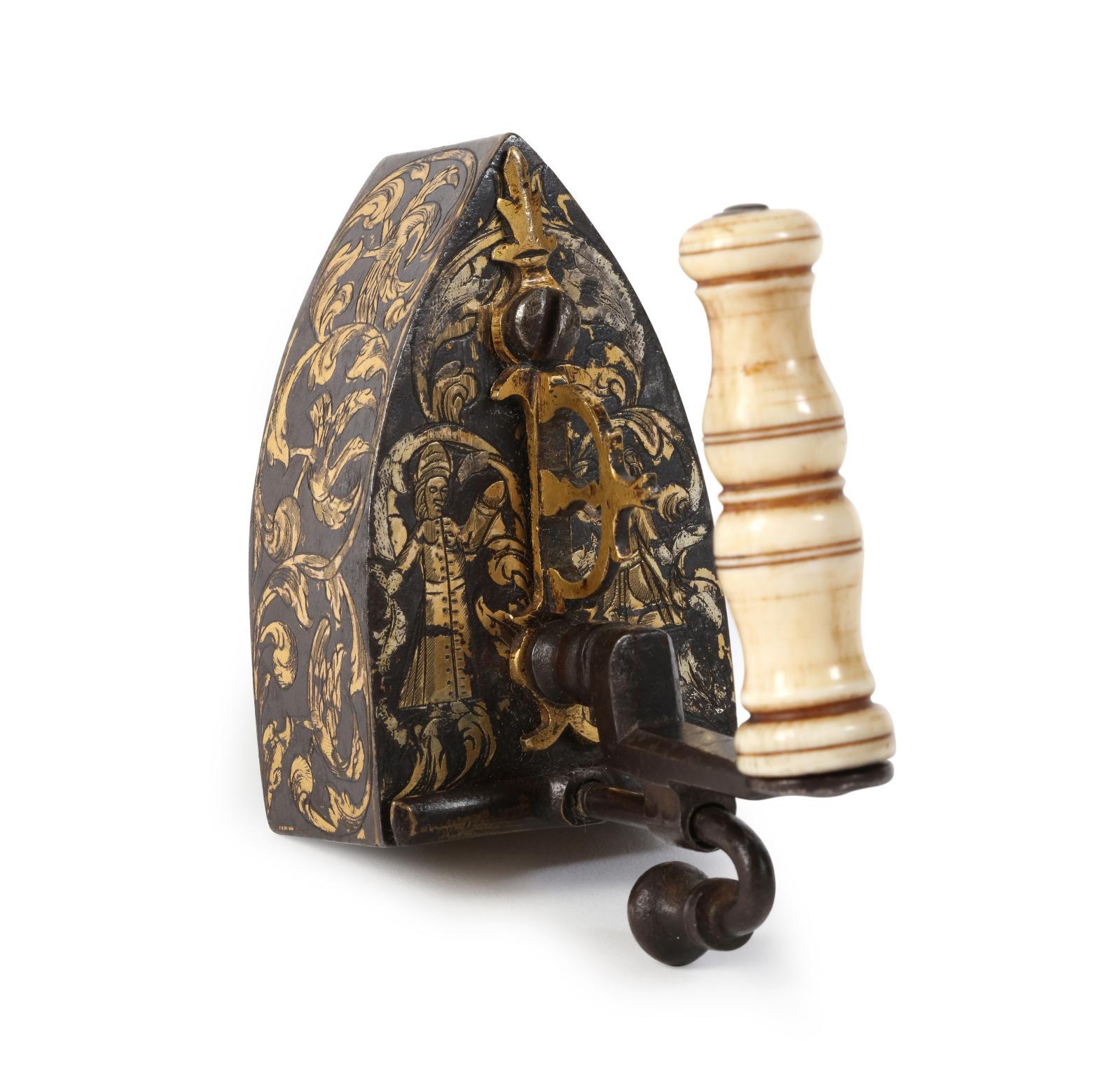 Époque LouisXV. Fer creux à repasser miniature, en fer forgé et gravé, à rehauts or, poignée en ivoire tourné assemblée sur un montant à retour conte