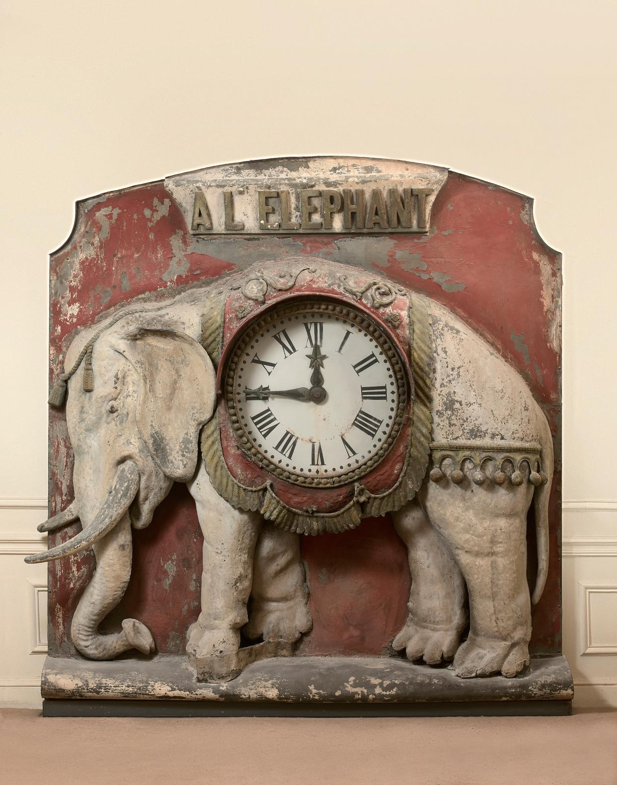 Vers 1840. Enseigne du fabricant de fournitures pour cafés et bistrots «à l'éléphant», zinc et tôle peints, présentant un éléphant paré, la panse abri