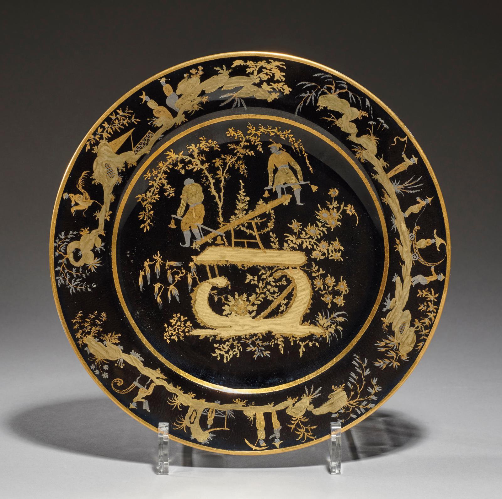 Sèvres. Assiette en porcelaine dure en or et platine sur fond noir décorée de deux Chinois d'après la gravure de Jean Pillement, diam. 24cm. Estimati