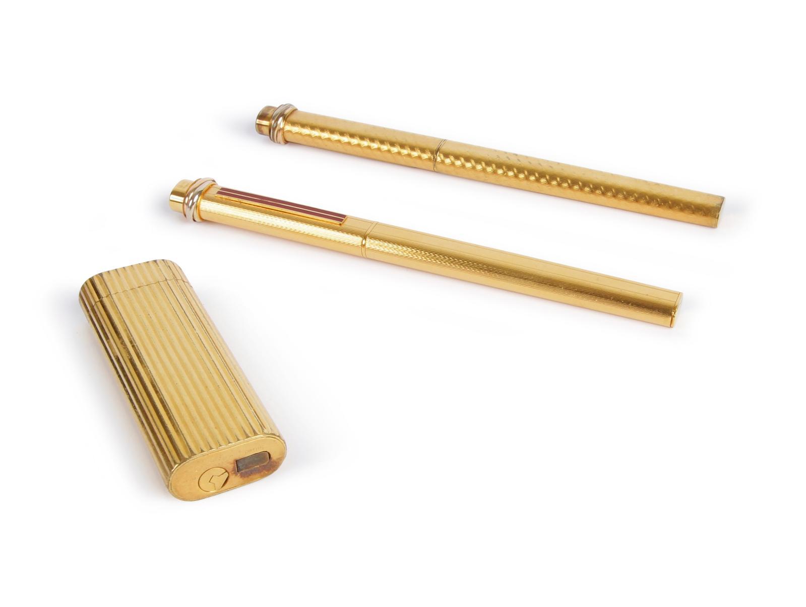 Cartier, lot de deux stylos à bille et un briquet en métal doré guilloché. Paris, Drouot, Ader SVV, 13mars 2019, 224€.