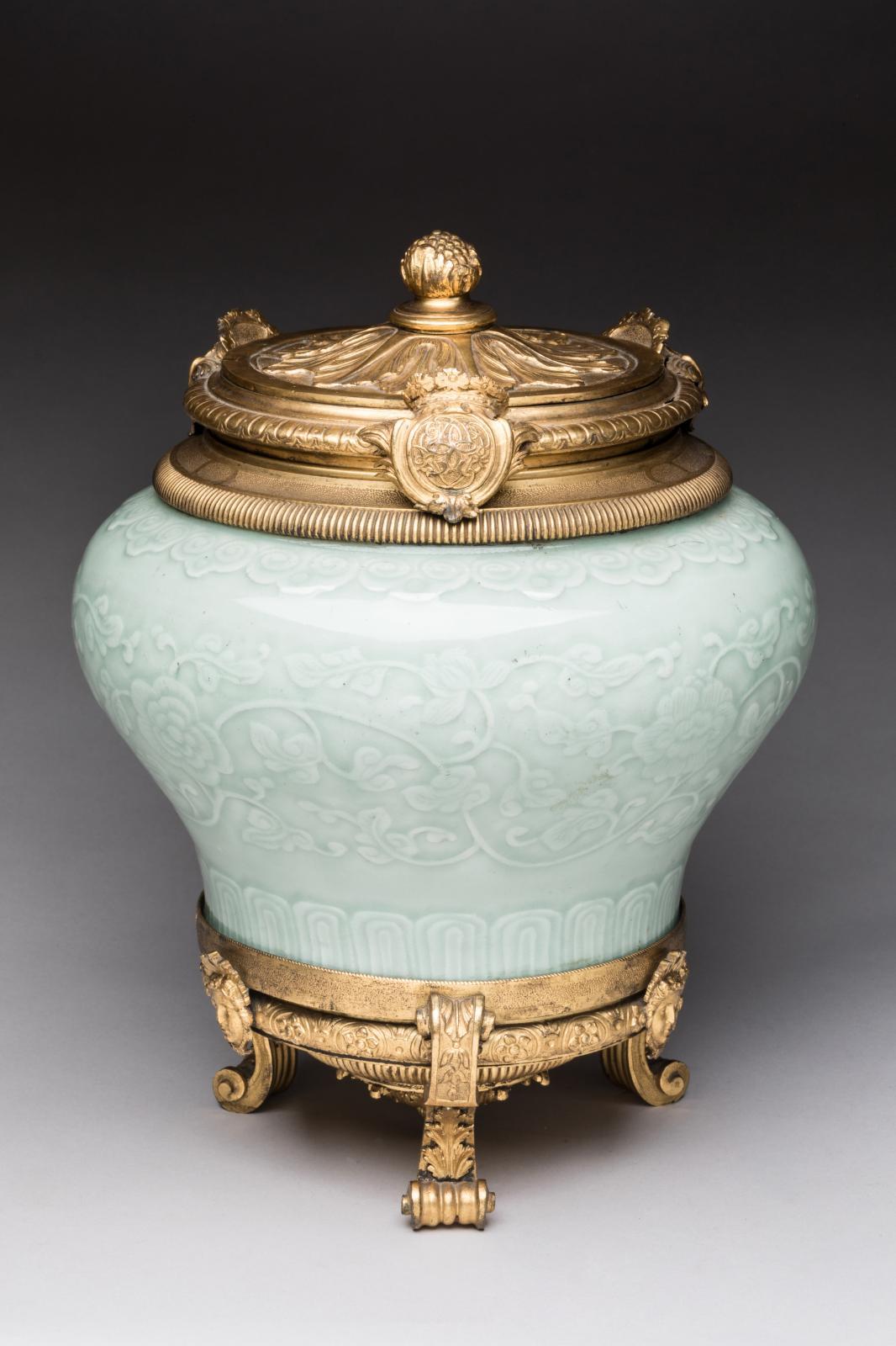 Vaseen porcelaine dite «céladon», monture en bronze ciselé et doré, couvercle centré d'une rosace, base tripode à crosses, culot godronné à rosace et