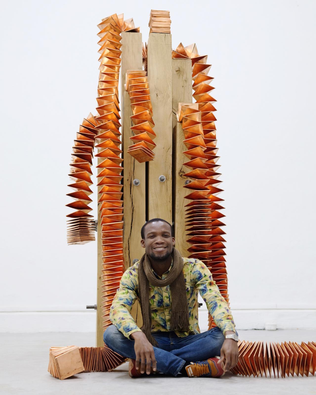 Kokou Ferdinand Makouvia (né en 1989), Eviono/Mother, 2018. L'artiste pose à côté de son œuvre, produite grâce à Ronan Grossiat, dans le cadre du prix
