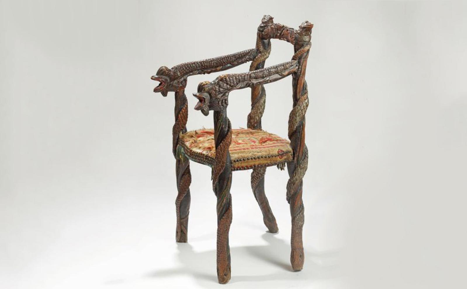 Probablement Berry, XIXesiècle. Fauteuil de sorcier en bois d'essences diverses, à décor sculpté polychrome de serpents, dragons aux serres d'aigle,