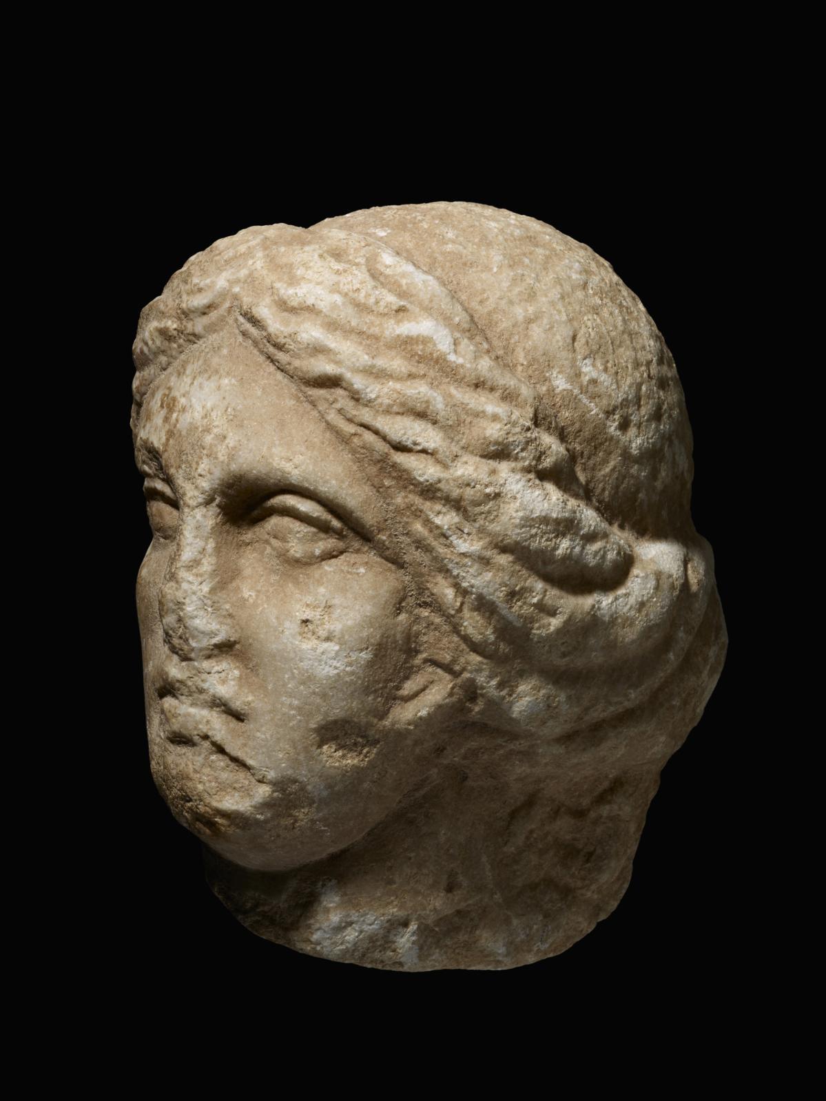 Tête féminine (Aphrodite?), fin de l'époque hellénistique, Ier siècle av. J.C.- Iersiècle apr. J.C, marbre à patine rougeâtre, h.22cm. Provenance