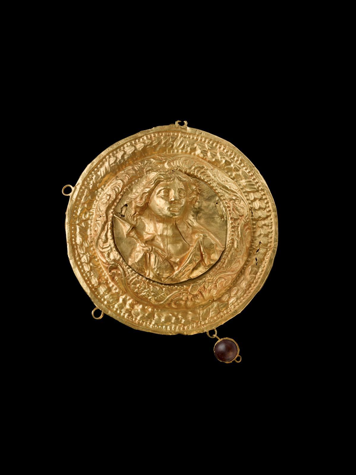 Art hellénistique, IVe-IIIesiècleav.J.-C. Ornement de coiffure circulaire au buste de la déesse Artémis, or et pierre rouge, diam.8,2cm. Estimati