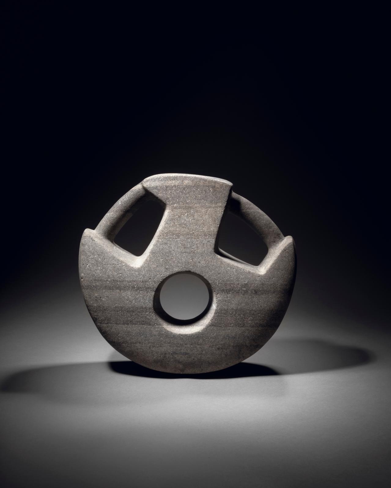 Culture veracruz, golfe du Mexique, 300-600 apr. J.-C. Manopla, dit «cadenas», pierre grise, h. 28,9, l. 30,8cm. Estimation: 40000/50000€