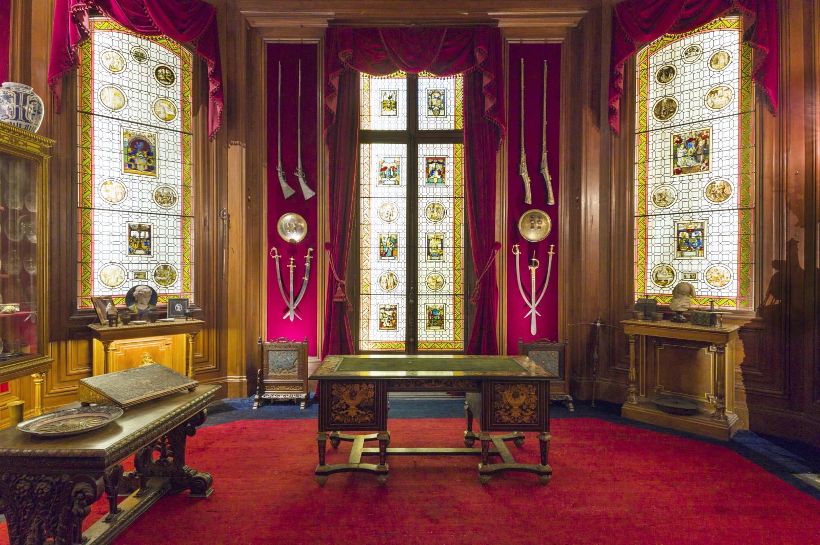 Des vitraux du XVIesiècle ont été incrustés dans les baies vitrées, encadrées d'une collection d'armes. Sur la console, l'Orpheline alsacienne, le ma