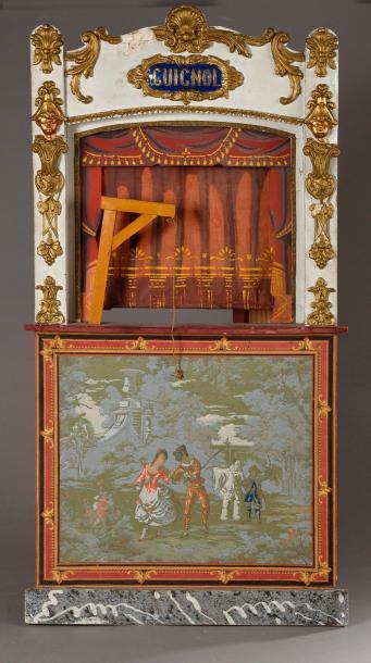 434€Petit théâtre «Guignol», début du XXesiècle, bois peint, composition dorée et papier peint, 97x50cm. Drouot, 9juin 2017. Le Floc'h OVV.