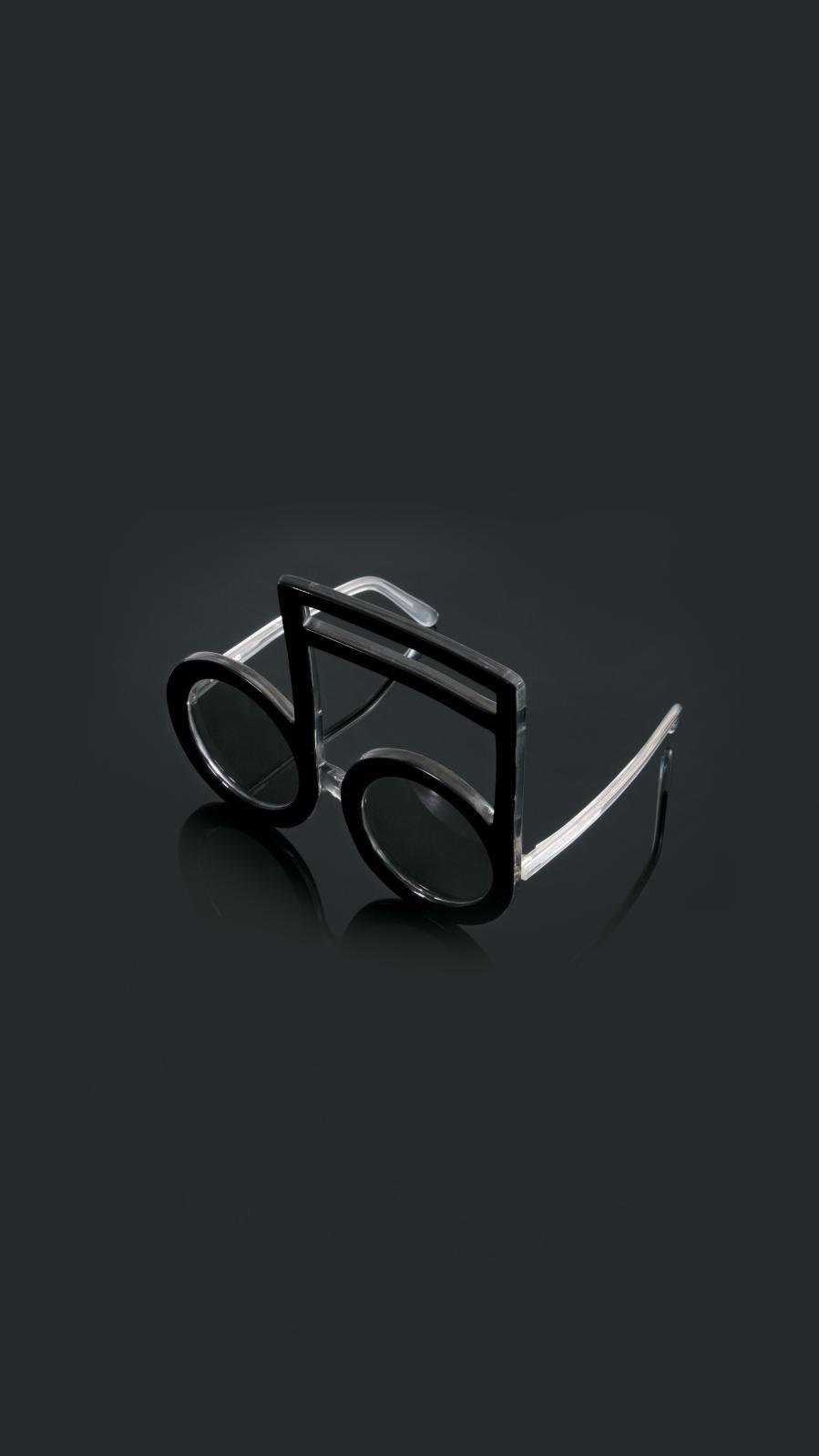 Pierre Marly. Paire de lunettes de soleil modèle «Double-croche», en acétate teinté noir, les branches translucides en partie pailletées gris, l'intér