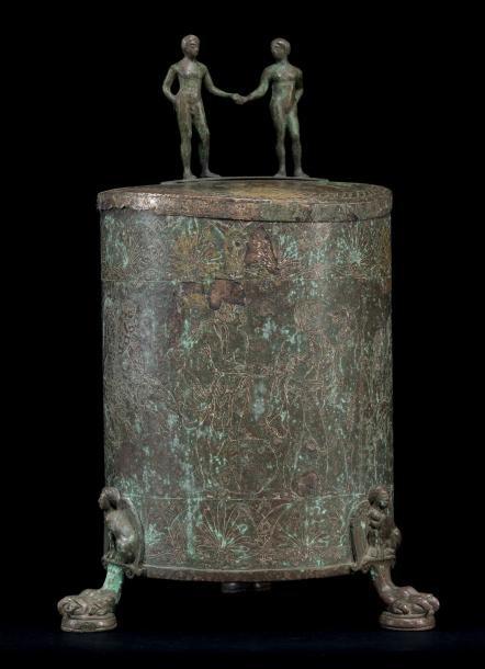 31926€Époque hellénistique, Ciste gravée d'une scène de victoire et de banqueteurs, couvercle surmonté de deux statuettes, argent, h. 43cm.Hôtel le