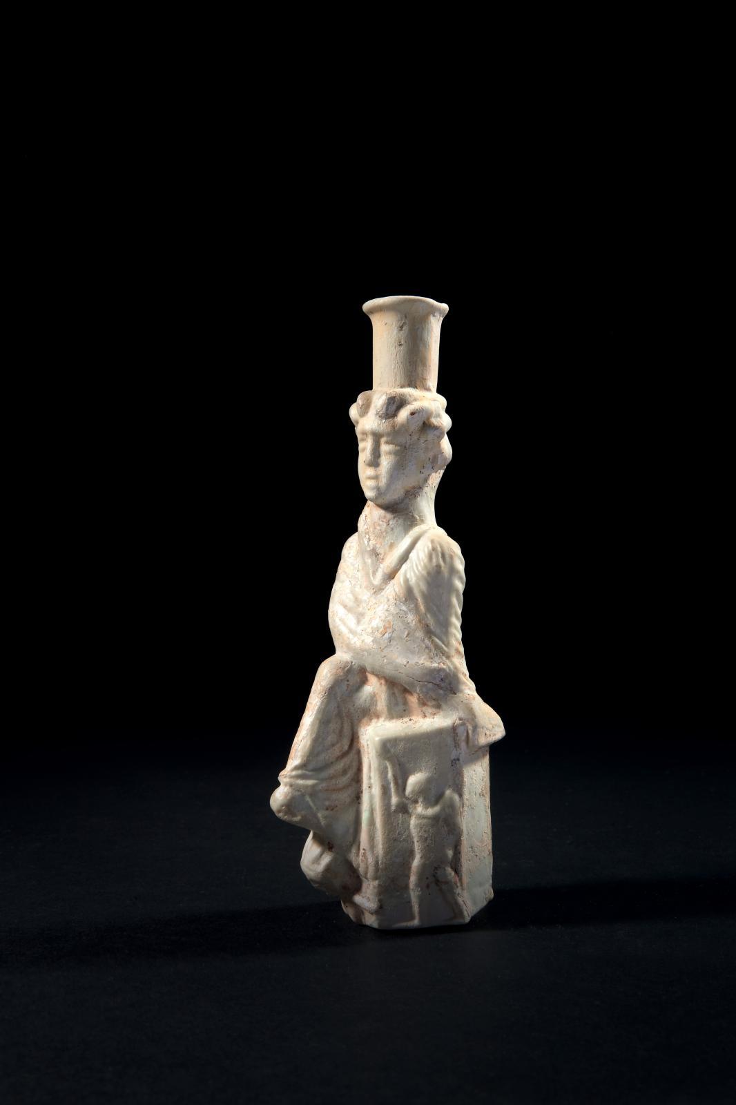 Art romain, IIe-IIIesiècle. Flacon représentant la Tyché d'Antioche en verre soufflé moulé blanc opaque, h.15,5cm.Estimation: 70000/80000€