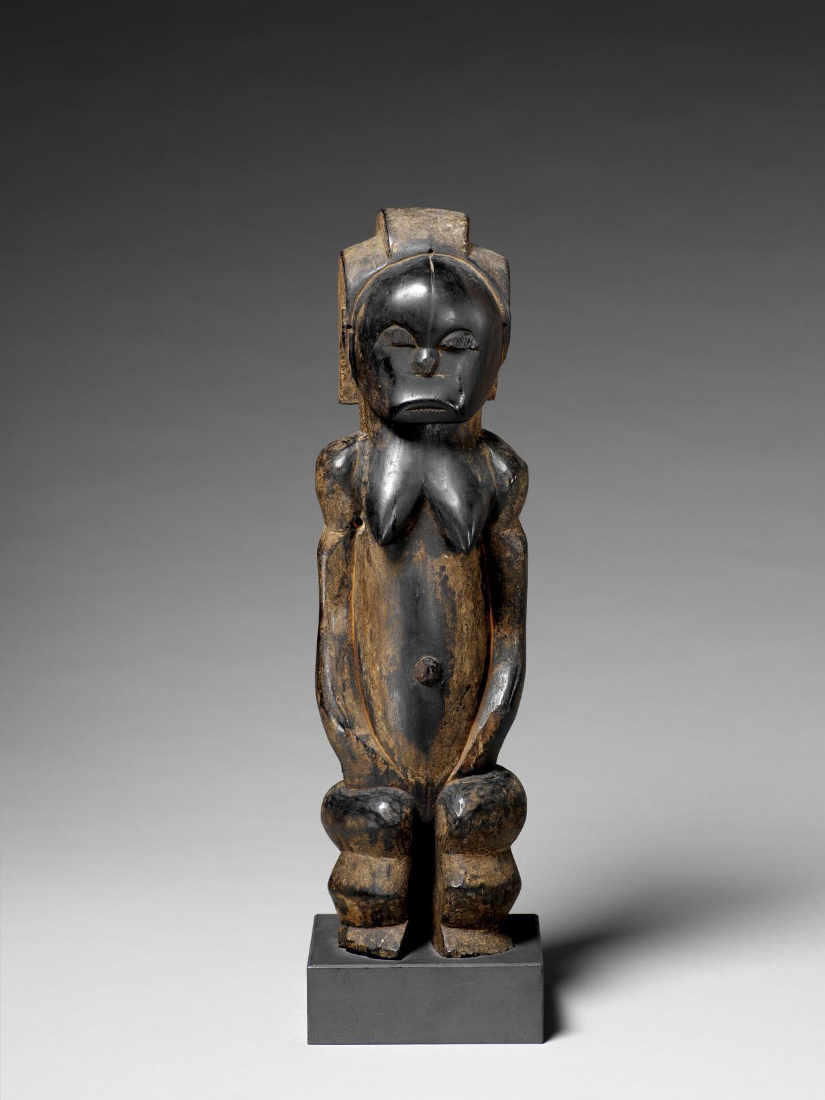 Statuette en bois anthropomorphe, figure féminine debout, les bras le long du corps. Cette sculpture était fixée sur la boîte contenant les ossements