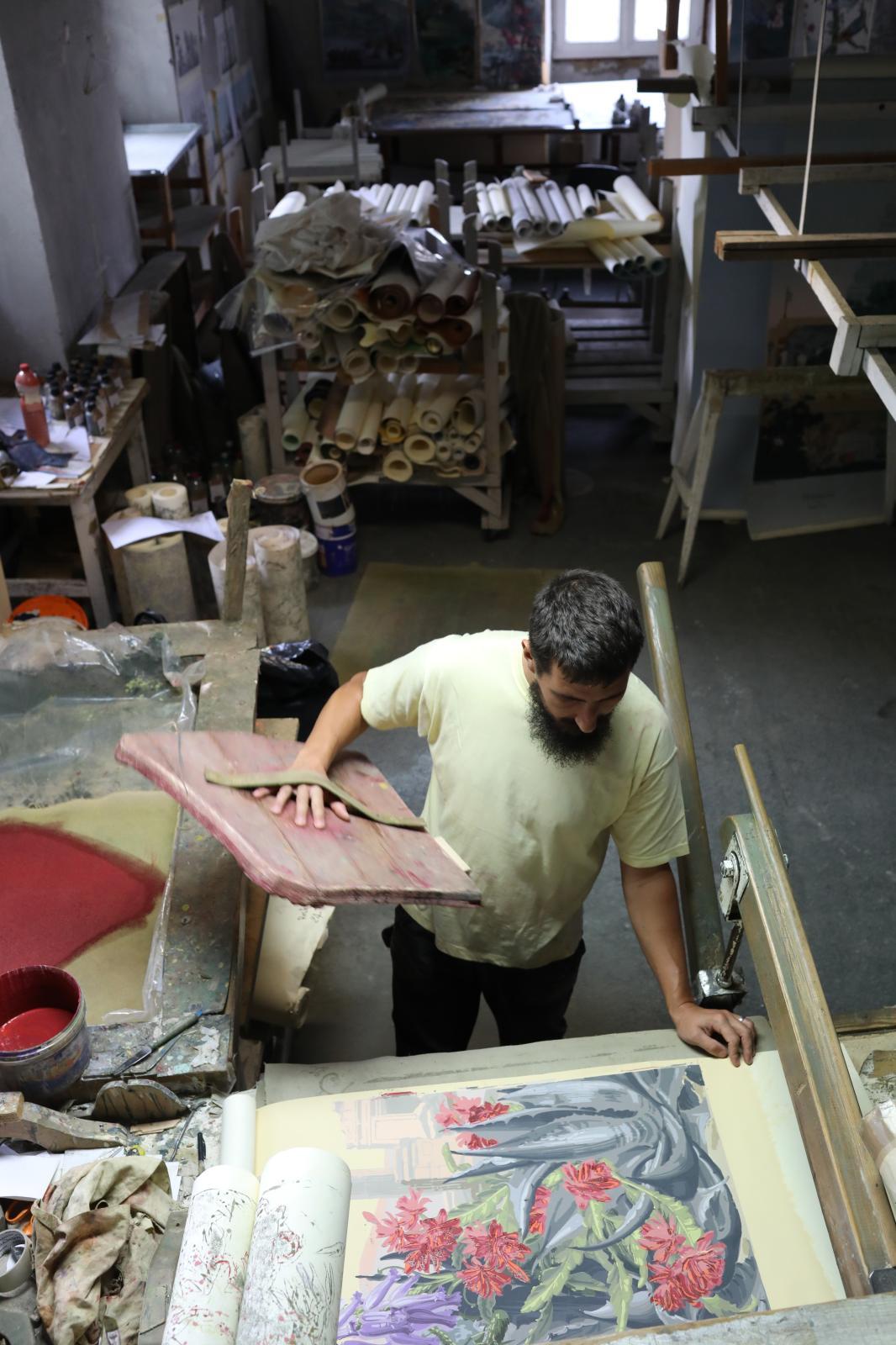 L'artisan imprime le motif sur le papier peint, complétant au fur et à mesure les différentes couches de couleur composant le décor.