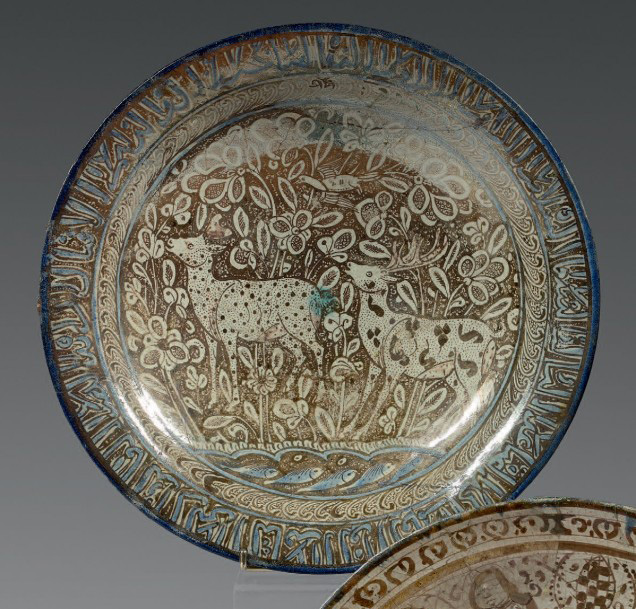 17864€Iran qadjar, XIXesiècle. Plat en céramique siliceuse à décor peint, à reflets métalliques et en bleu cobalt, d'un cerf et une biche dans des