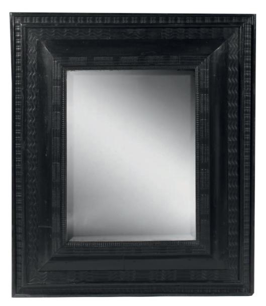 3098€Fin du XVIIe siècle. Miroir dans un cadre à profil inversé en placage de poirier noirci, à décor de filets ondés ou godronnés, fond de miroir a