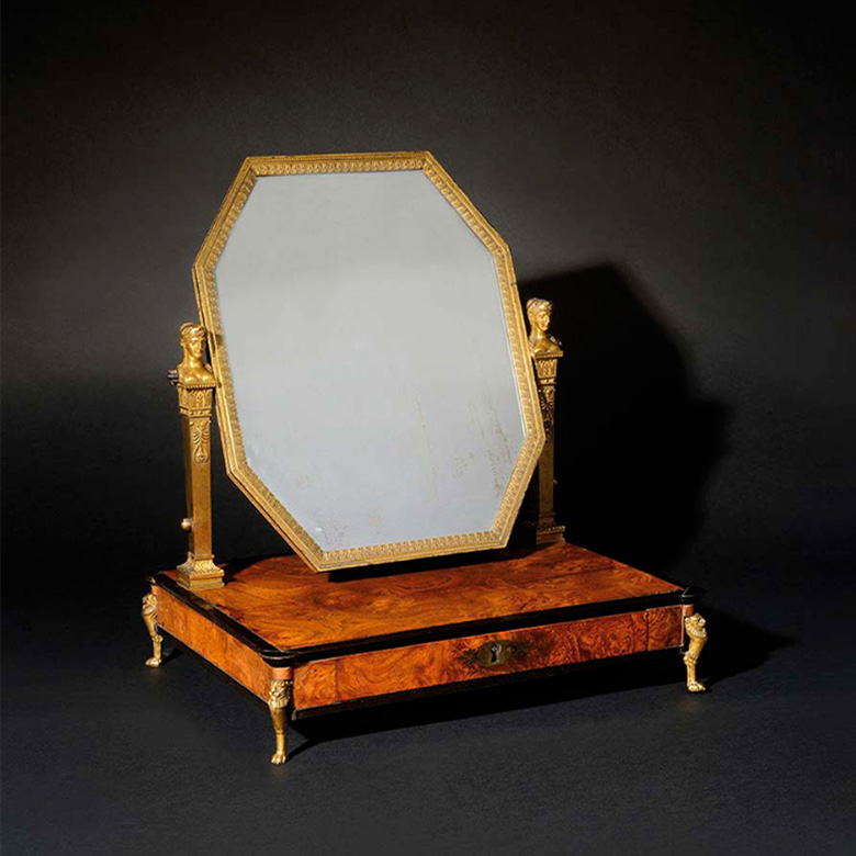 125000€ M.-G. Biennais, orfèvre de S.M.l'Empereur. Psyché au miroir octogonal supporté par deux montants en gaine. Meuble en placage de loupe de fr