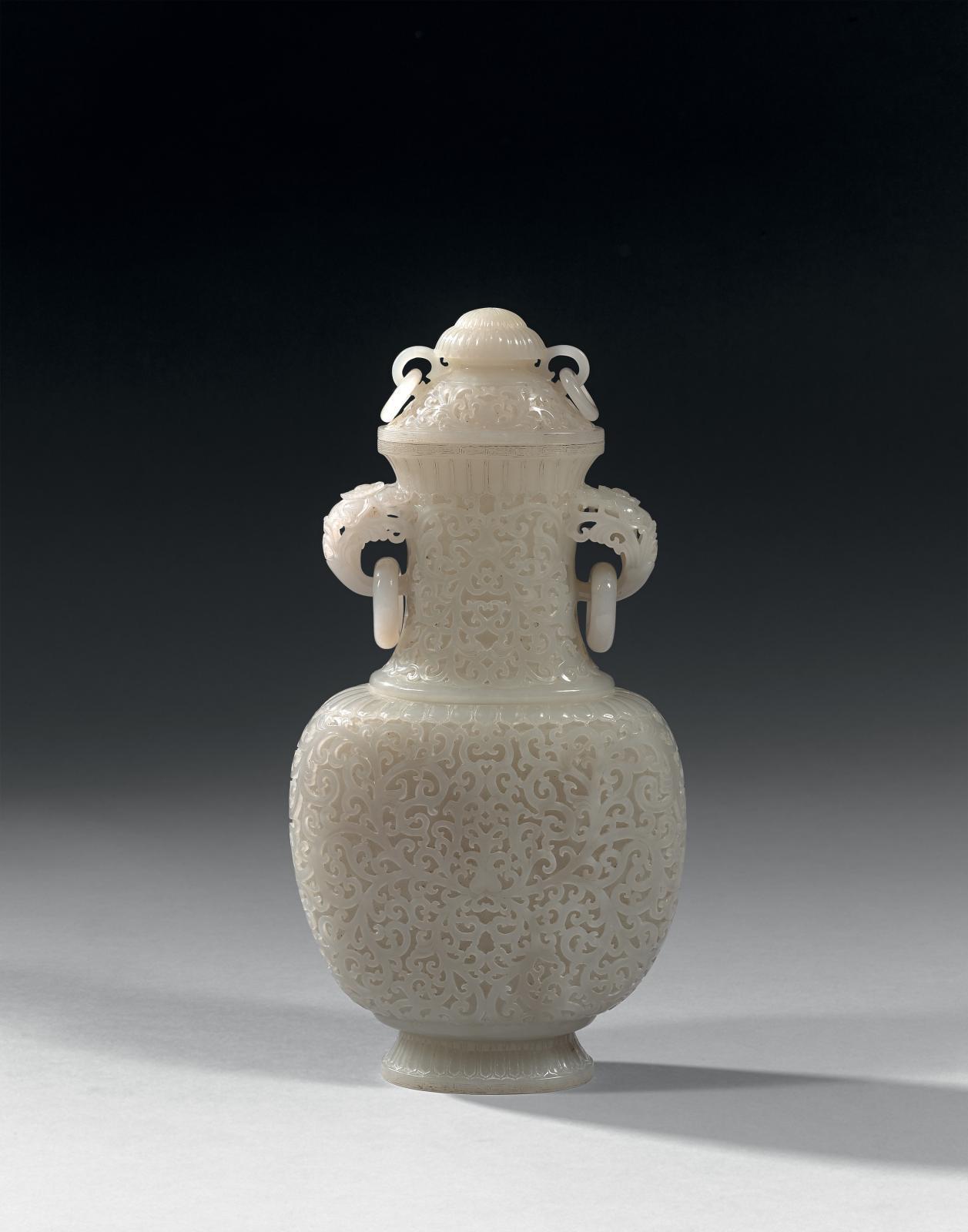 Chine, première moitié du XXesiècle. Vase couvert en jade blanc de forme balustre à panse aplatie, anses en forme de têtes d'éléphants, décor de fleu