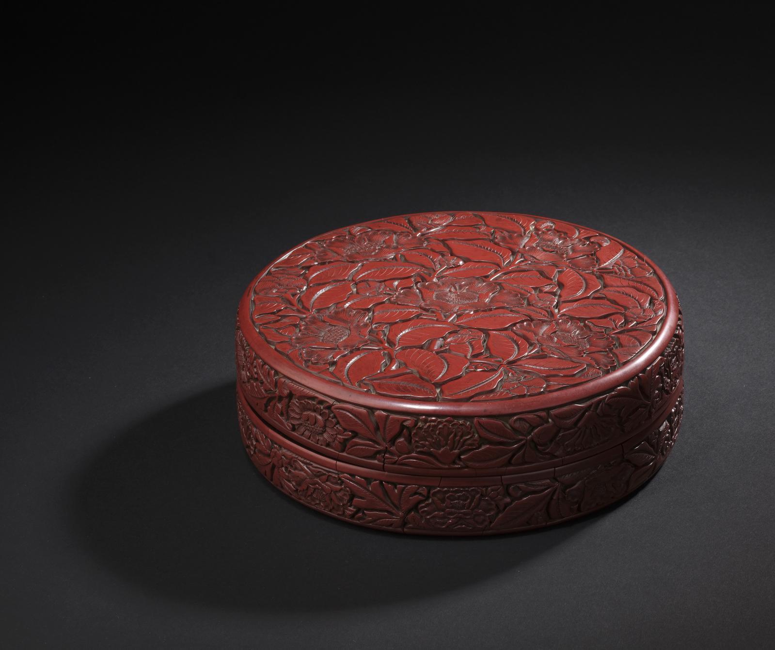 Chine, début XVesiècle. Boîte de forme ronde en laque rouge sculptée de cinq fleurs de camélia et bourgeons dans leur feuillage sur fond