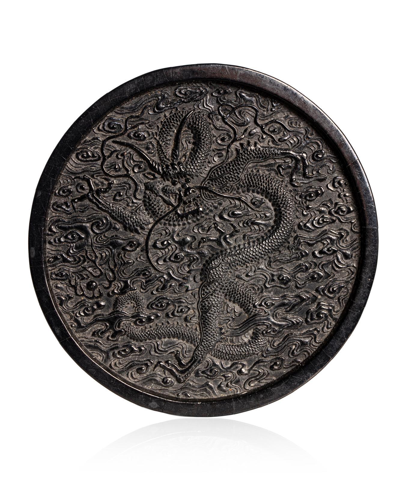 Chine, époque Qianlong (1735-1796). Pain d'encre circulaire, à décor d'un dragon de face parmi des nuages stylisés, de caractères archaïsa