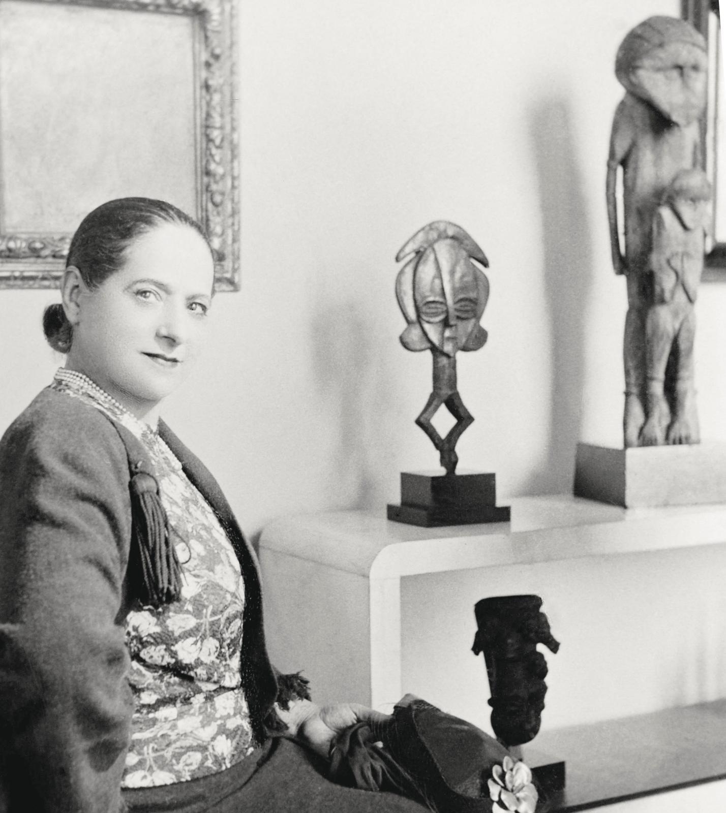 Helena Rubinstein posant devant des objets de sa collection, 216, boulevard Raspail, Paris, vers1930. © Studio Lipnitzki/Roger-Viollet