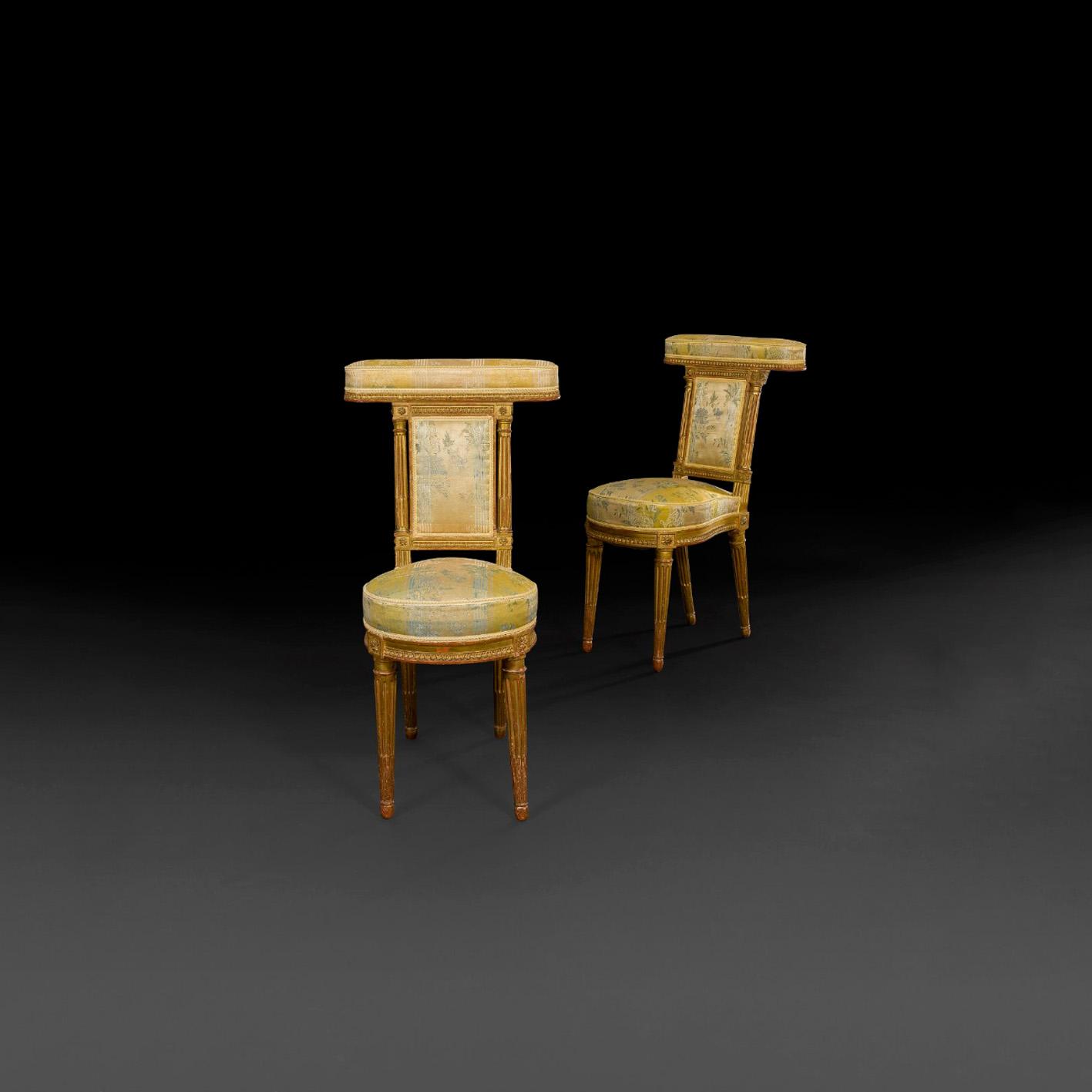 2432€ Époque LouisXVI, paire de chaises ponteuses en bois redoré sculpté de rais de cœurs, assise en fer à cheval, pieds fuselés, h.89