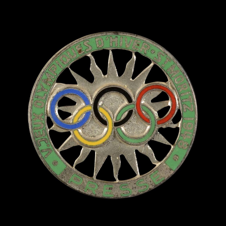 425€ Badge presse pour les Vesjeux Olympiques d'hiver à Saint-Moritzen 1948, métal doré, argentéet émaillé, diam.32mm.Drouot, 12déc