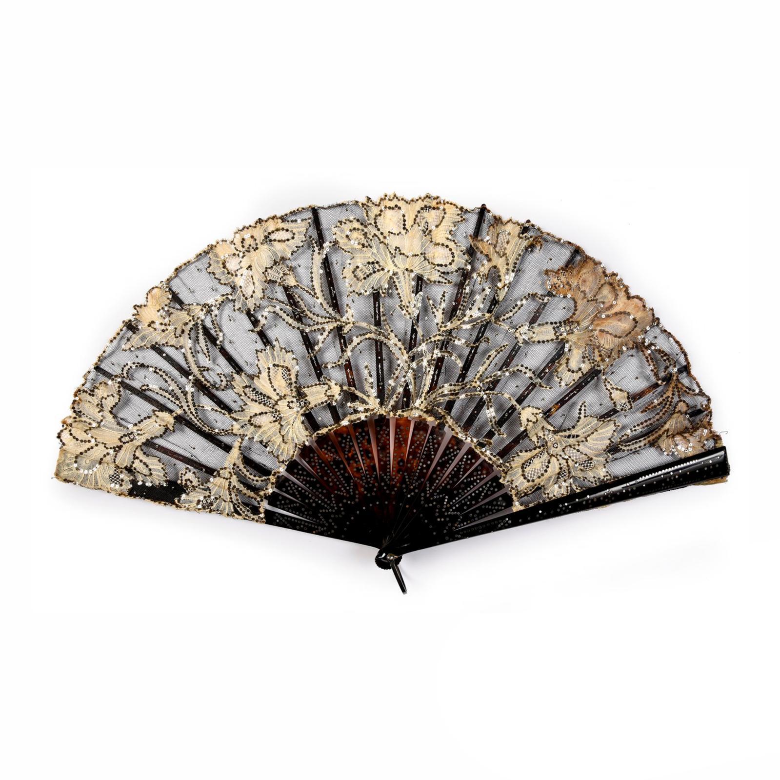 885€ Vers 1900. Les Œillets d'argent, éventail plié, feuille en tulle, monture en écaille brune incrustée de paillettes d'acier, bélière,