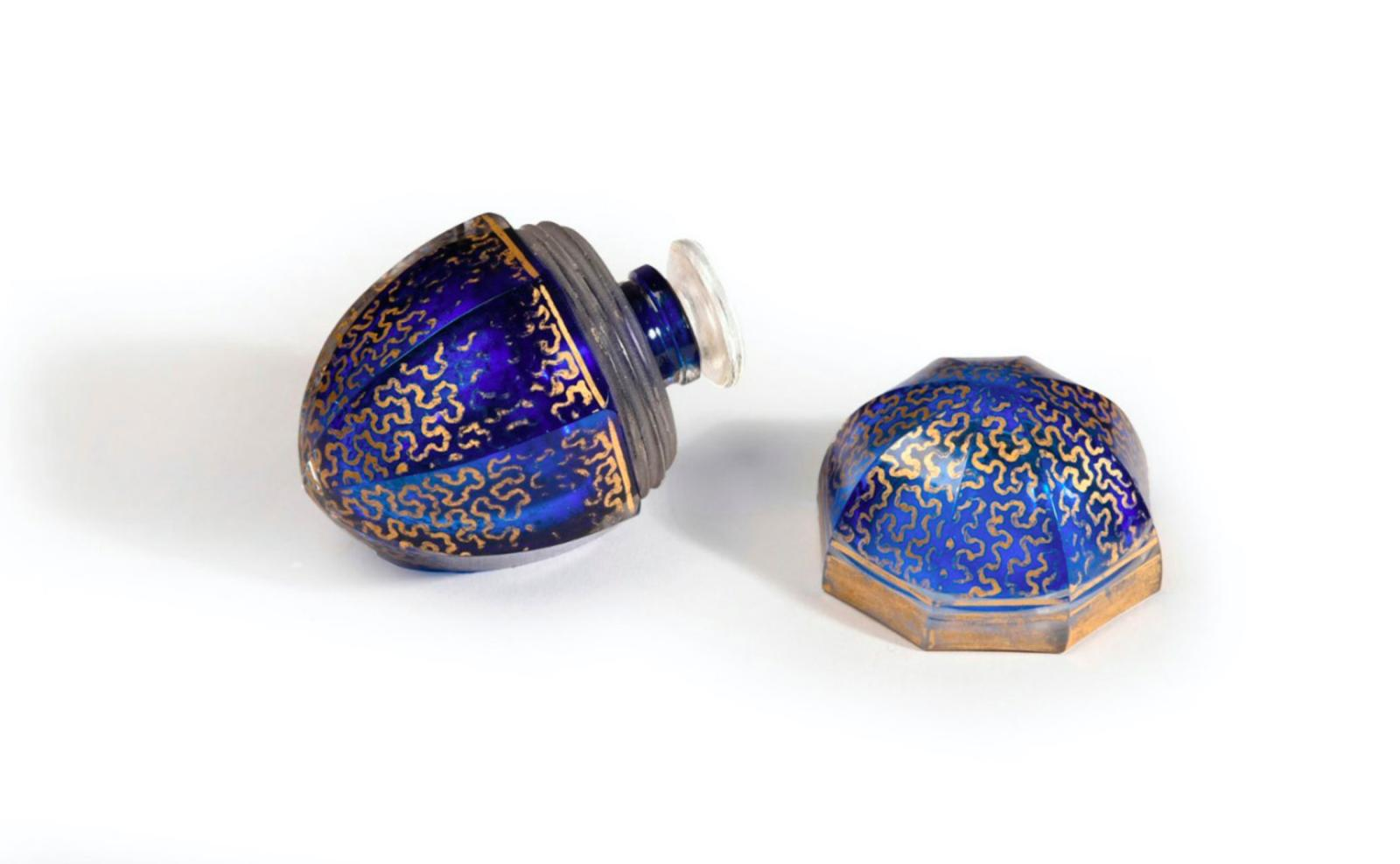 Coty, 1920s, perfume bottle made of colourless pressed moulded glass, with midnight blue enamelling, gold decoration and a glass screw cap
