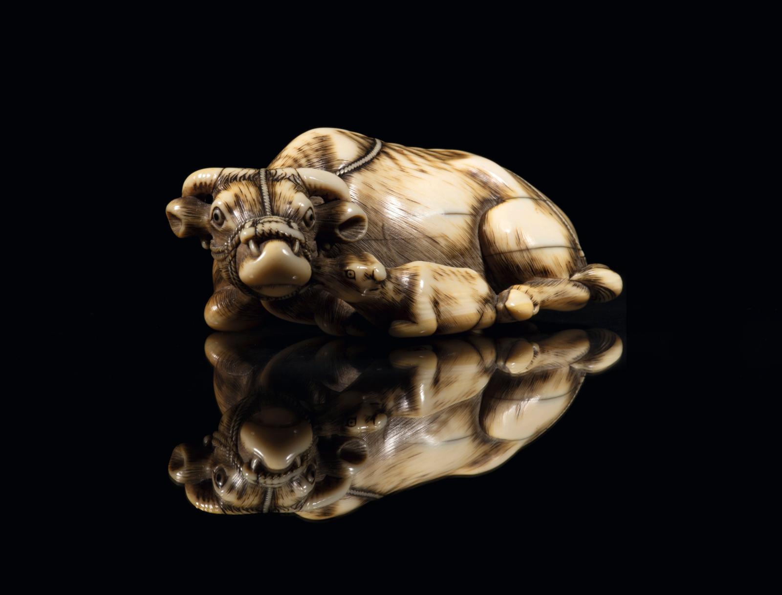 Japon, époque Edo (1603-1868), XVIIIesiècle. Netsuke en ivoire, vache couchée, son veau auprès d'elle, les yeux incrustés de corne brune, signé Tomot