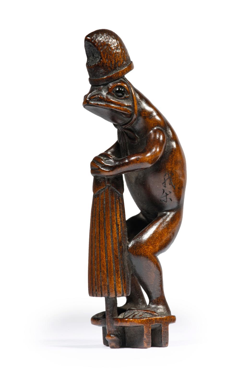 Japon, époque Edo (1603-1868), XIXesiècle. Netsuke en bois, grenouille debout portant un eboshi, des geta et une ombrelle, yeux incrustés de corne br