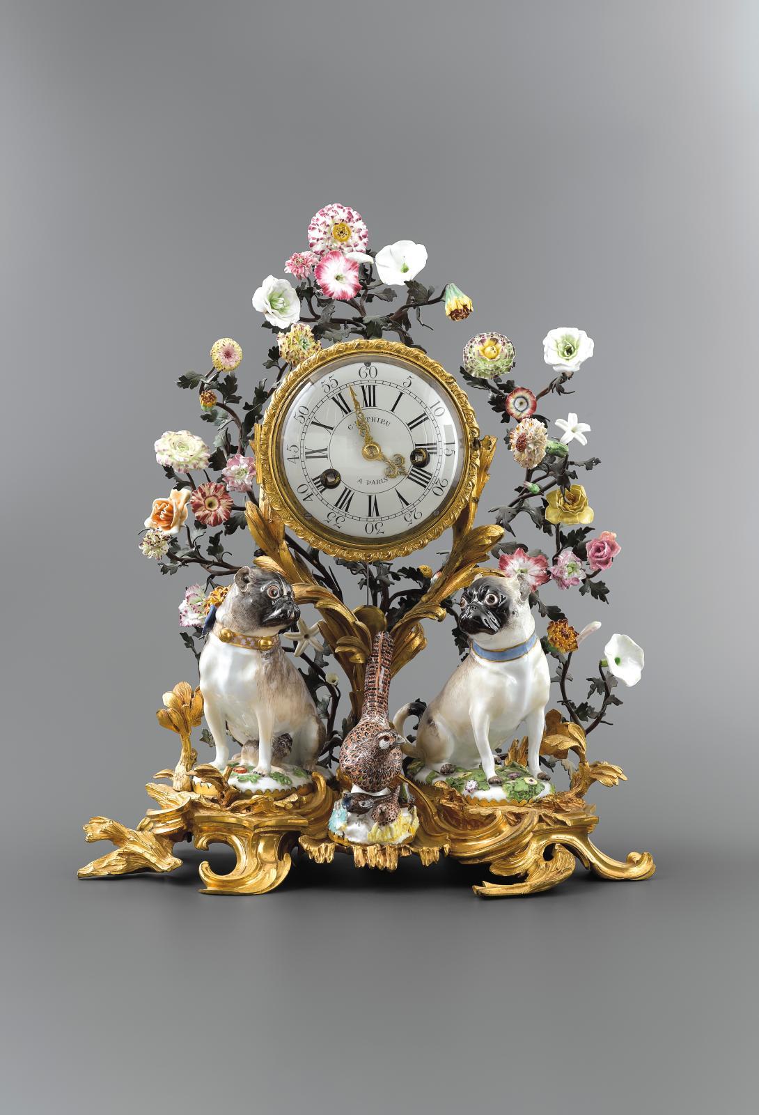 Pendule aux carlins. Porcelaine dure de Meissen à décor polychrome montée en bronze ciselé et doré, fleurs en porcelaine tendre française,