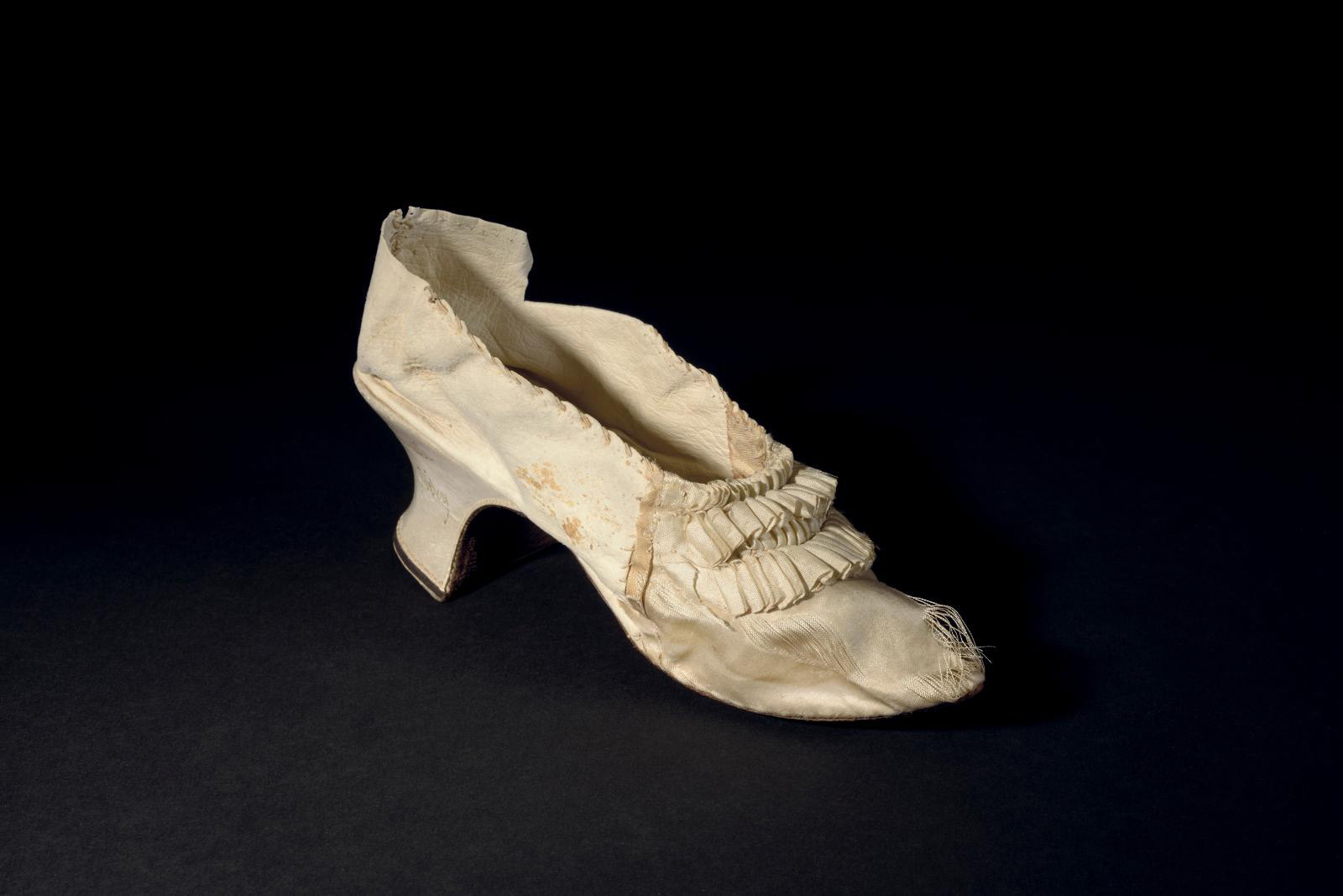 Colored shoe, with the toe section in silk and the back section in kid, decorated on the front with four superimposed pleated ribbons, lea