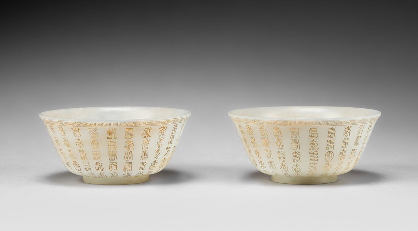 Chine, époque Qianlong (1736-1795). Paire de bols en néphrite blanche à décor incisé et doré de 120 caractères «shou» stylisés, l'intérieu