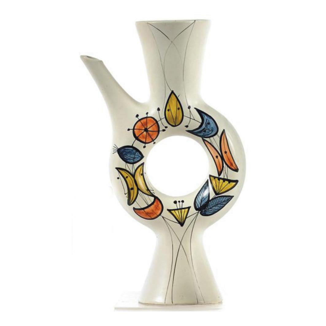 4369€ Roger Capron, verseuse «anneau» en terre cuite à décor polychrome de fleurs, papillons et visages stylisés, h.33cm.Drouot, 26oc