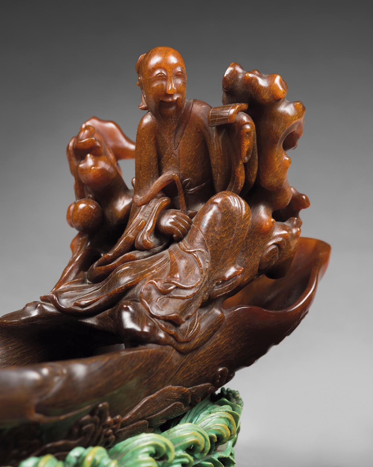 Chine, XVIIe-XVIIIesiècle. Coupe libatoire en corne de rhinocéros de couleurs miel et foncée, figurant Zhang Qian assis dans sa barque en