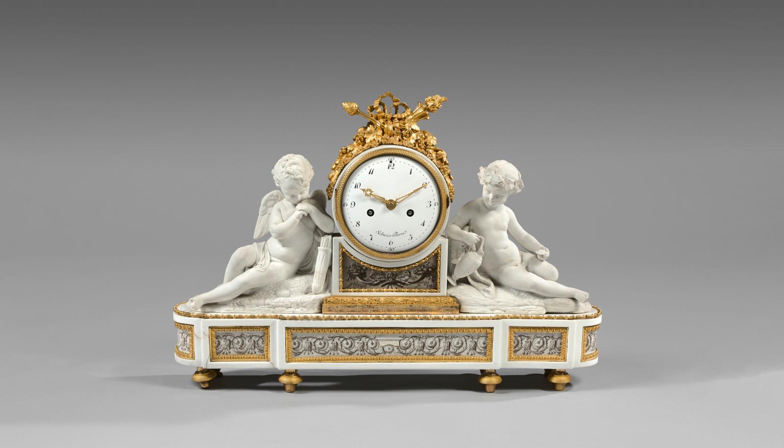 Pendule ornée d'un amour avec Bacchus enfant en biscuit et bronze doré,base en porcelaine dure ornée de rinceaux «Salembier», Manufacture