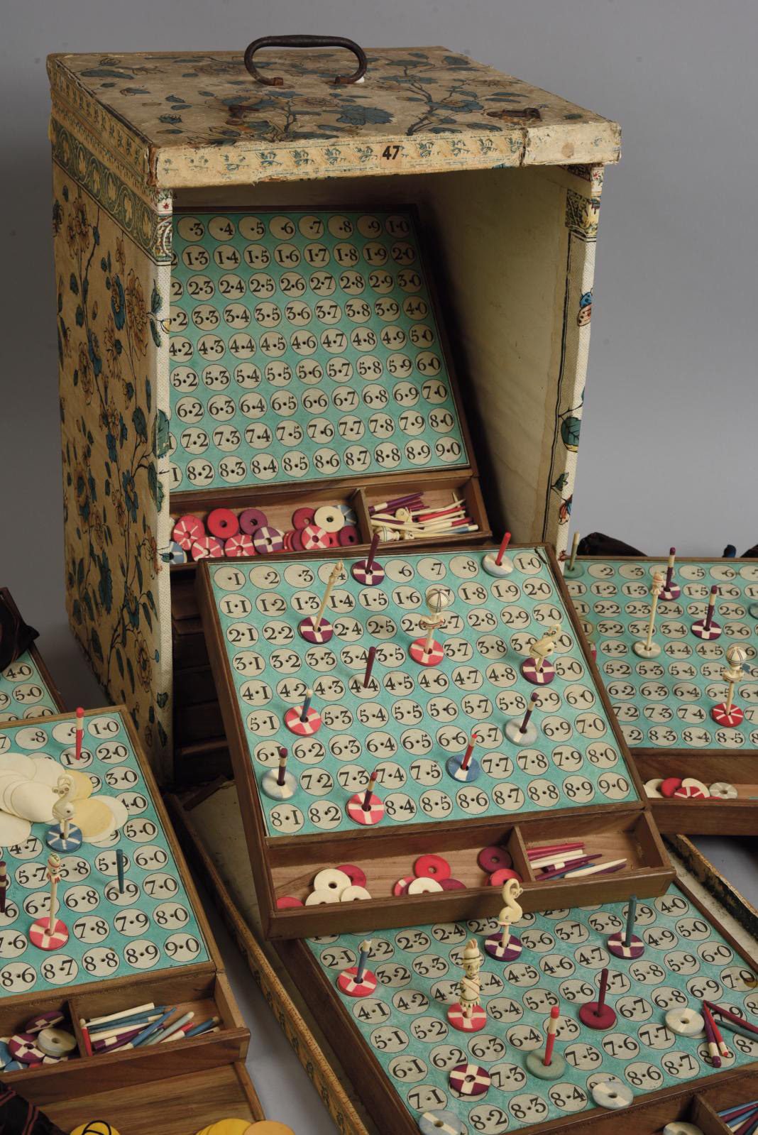 "Late 18th-century French work. ""Loto du Dauphin"" lottery game, comprising twelve trays, some with their stained bone tokens, still in its"