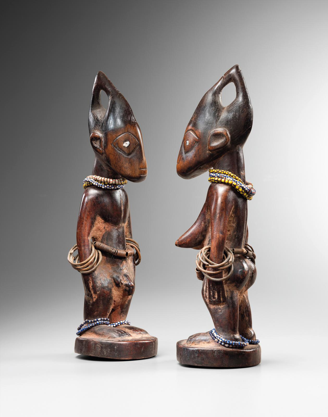 Ibeji figures from Nigeria, wood, beads, metal, h. 29 and 28.5 cm (11.4 and 11.2 in), Galerie Didier Claes.Courtesy of Galerie Didier Clae