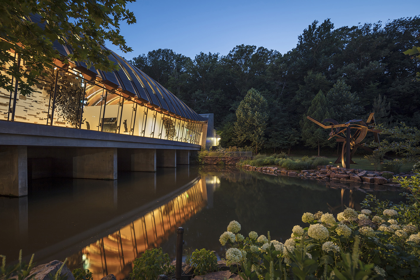 View from north lawn to gallery bridge with Lowell's Ocean, steel sculpture by Mark di Suvero.Image Courtesy of Crystal Bridges Museum of