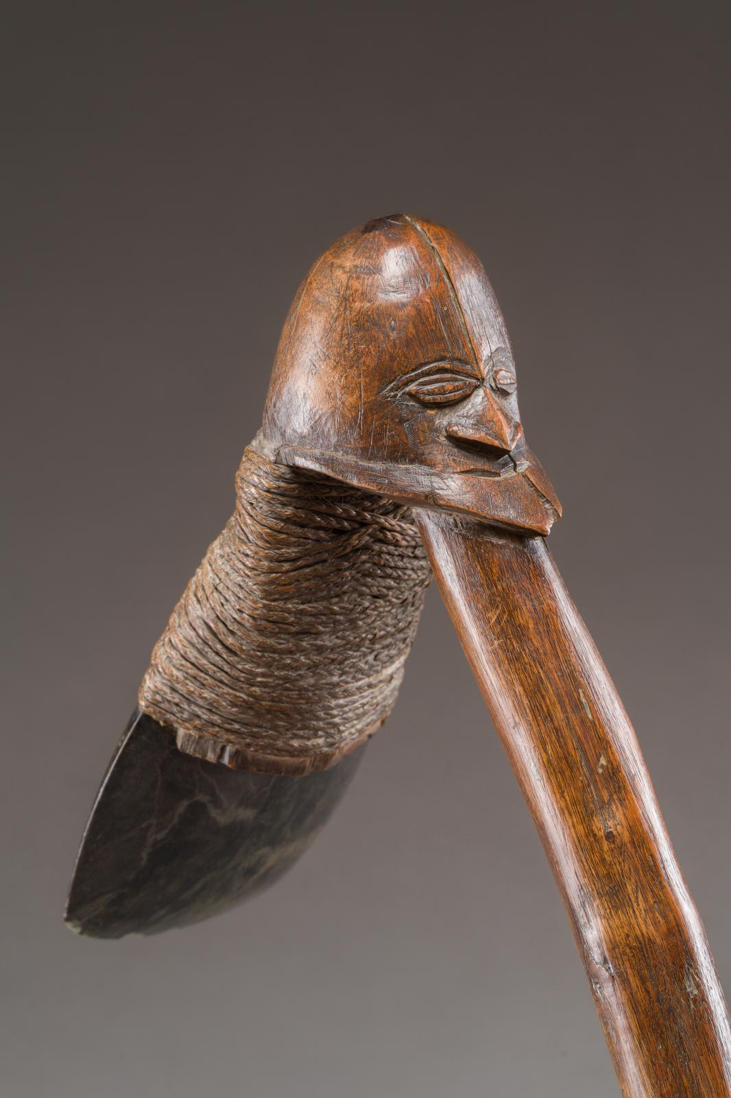 Melanesia, New Caledonia, Kanak people, 19th century. Adze featuring the head of an ancestor, wide serpentine blade held on with braided p