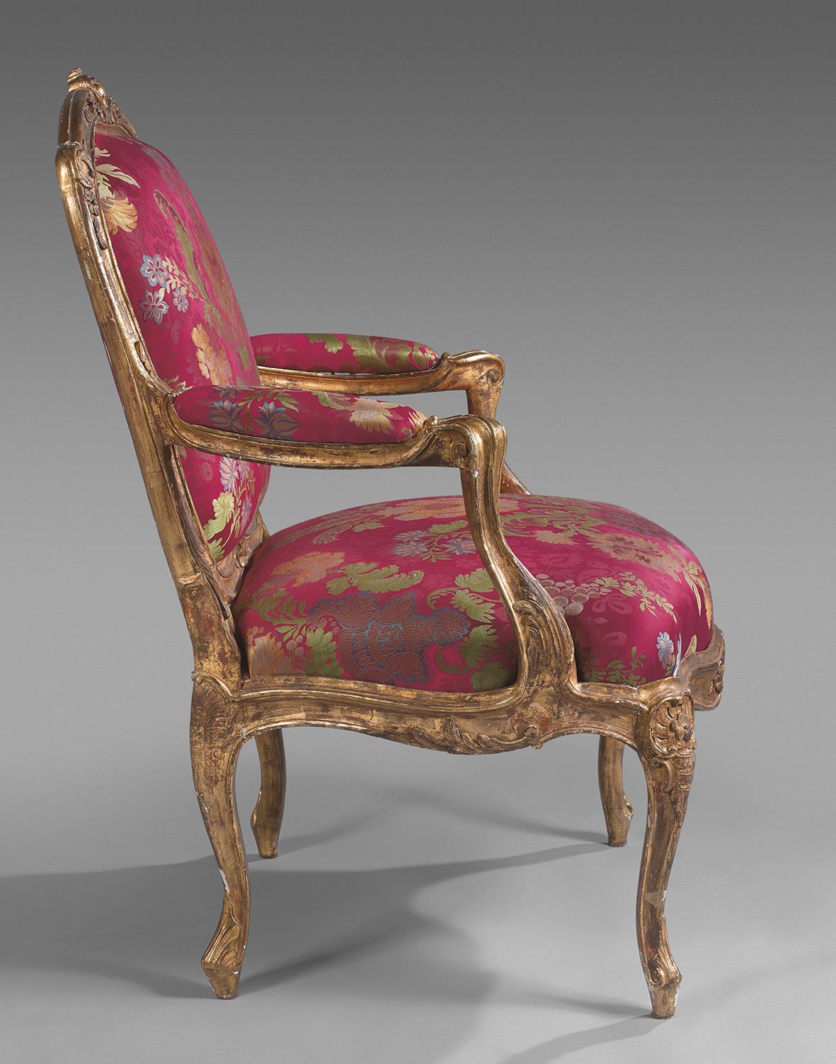 Ce fauteuil à châssis fait partie d'une suite de six –dont deux sont estampillés «Tilliard»— en hêtre doré sculpté de grenades et cartou